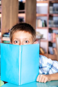 Library: amazed boy hiding behind book